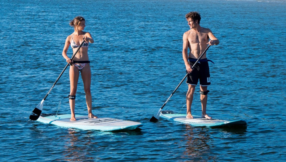 Couple riding SIC SUP boards