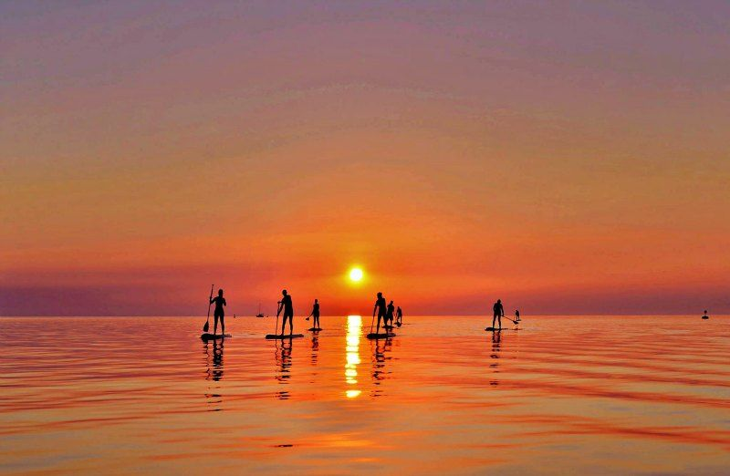 Group of people on their SUP during social sunset paddle