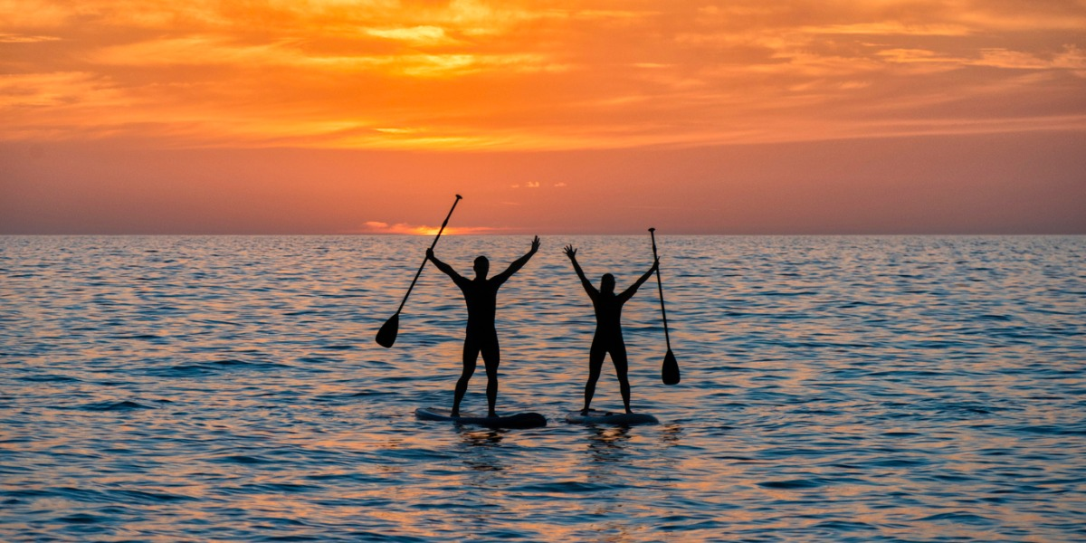 Two people on standup paddle board at sunset