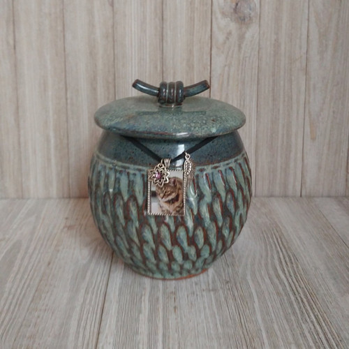 Handmade ceramic textured blue green pet urn.  Urn capacity 40 cubic inches. Small heart carved on the bottom of the urn.
