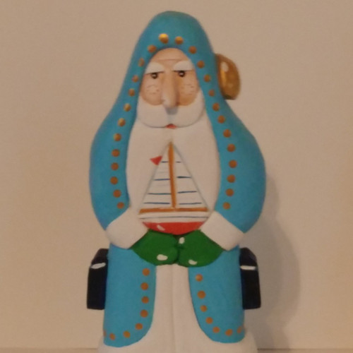 Turquoise Wooden Hand carved Santa Claus holding a sail boat. Made artist Bob Smith