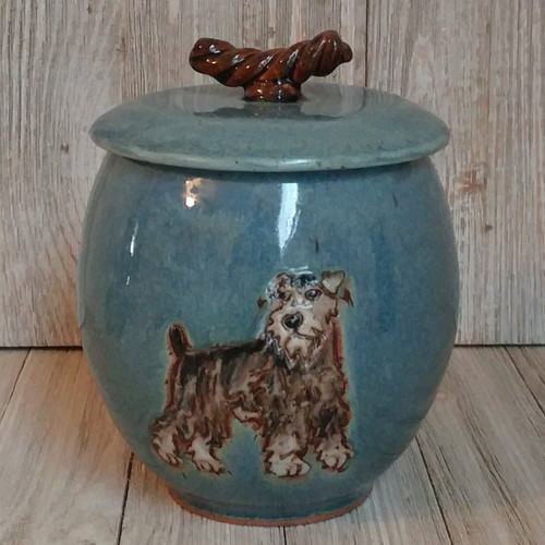 A handmade ceramic cremation dog urn with a Schnauzer dog rendered into the front of the urn. The urn capacity is 49 cu.