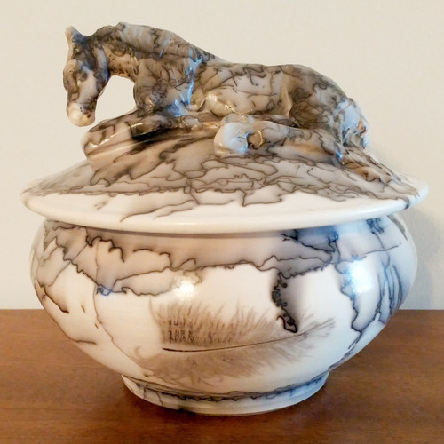 An unique and stunning handmade ceramic horse hair vessel with sleeping horse sculpted onto the lid of the vessel. The process includes using horse hair and a feather that is represented with the black lines into this beautiful memorial for your beloved horse or pony.