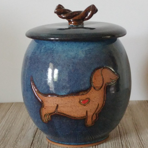 Handmade ceramic cremation pet urn for a Dachshund dog. This one of a kind ceramic dog urn has a Dachshund dog rendered by hand by an artist on to the front of the urn.