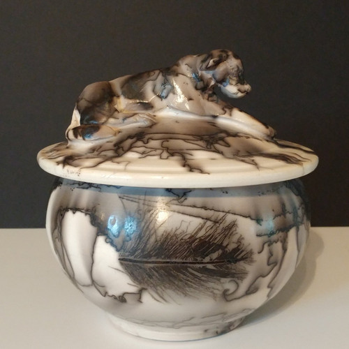 Black and white porcelain dog urn with sculpted dog on the lid of the urn. Made individually by an American Artist.