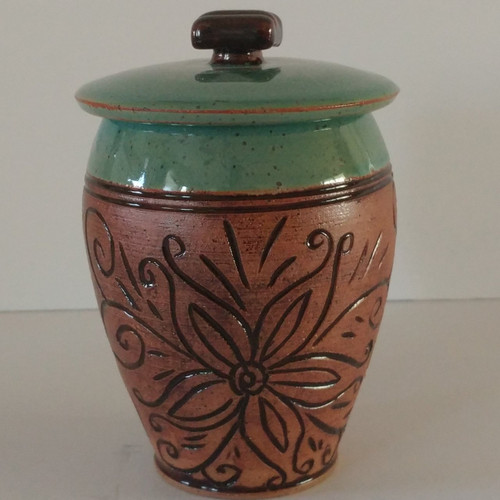 Small floral carved handmade ceramic pet urn. The urn is hand carved with a lovely floral motif going all around this cremation urn. Cubic capacity of 24 cu.