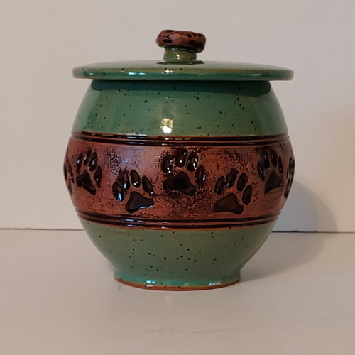 Handmade ceramic cremation pet urn in a green glaze with a band of paw print design center.