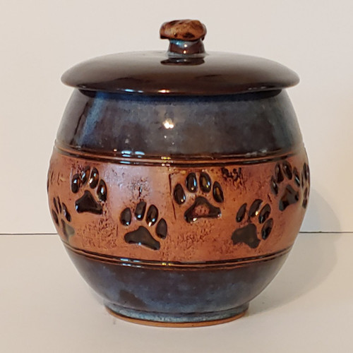 Medium size handmade ceramic ash pet urn with a band of embossed paw prints going completely around the urn.
