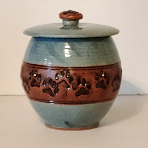 Medium size handmade ceramic light blue glazed pet urn with a band of paw prints going all around the dog urn.