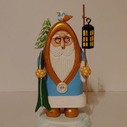 Hand carved wooden Santa by artist Bob Smith. The Santa is painted in turquoise and gold colors