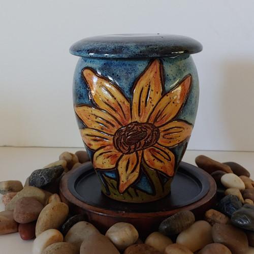 Small blue handmade ceramic keepsake urn with yellow sunflower.