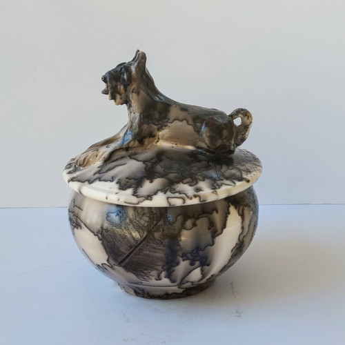 handmade ceramic Schnauzer dog urn with a sculpted Schnauzer on the lid of the urn. The urn is created using a horse hair processes.