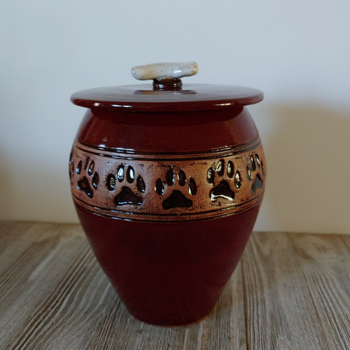 Red handmade ceramic dog urn with paw prints and dog bone lid.