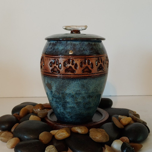 dark blue handmade ceramic dog urn with paw prints with dog bone on lid.