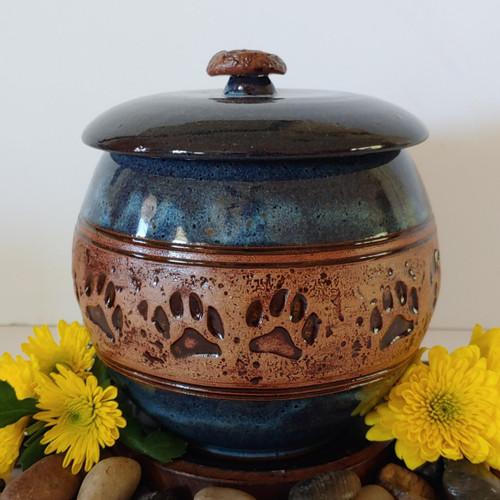 Handmade round dark blue ceramic dog urn with paw prints
