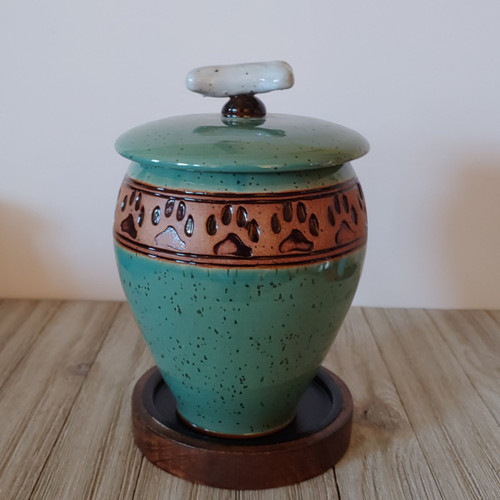 Tall green dog urn with dog prints and dog bone final on the lid of the urn,