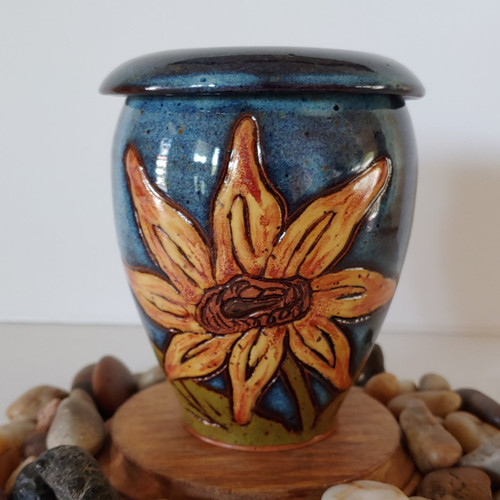 Keepsake yellow sunflower urn with dark blue glazed background color.