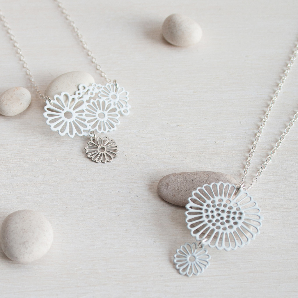 Daisy pendants with an extra daisy drop hanging at the base of pendant.