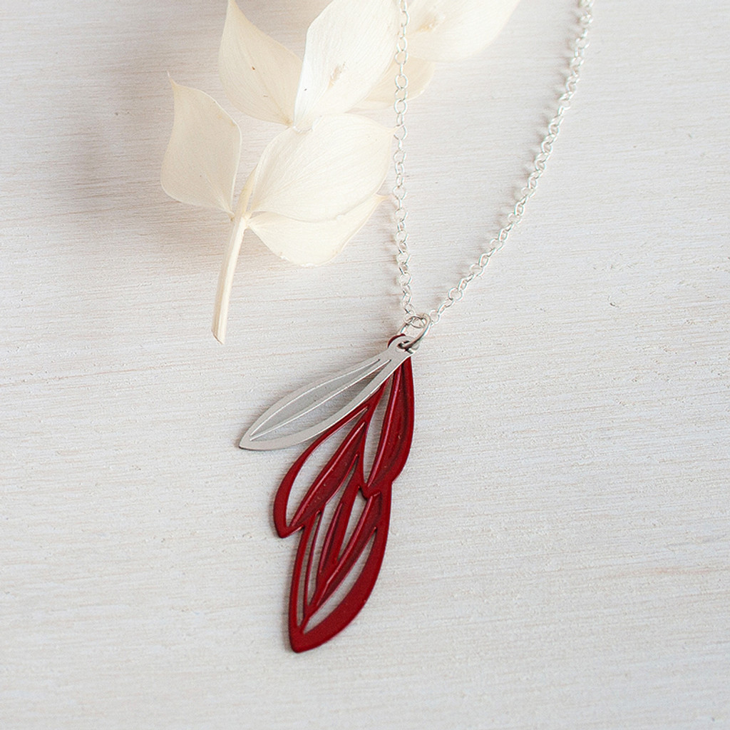 Elegant layered leaf pendant in red based on the varied leaves of native Eremophila plants  Made from stainless steel with contrasting powdercoated colour and raw steel