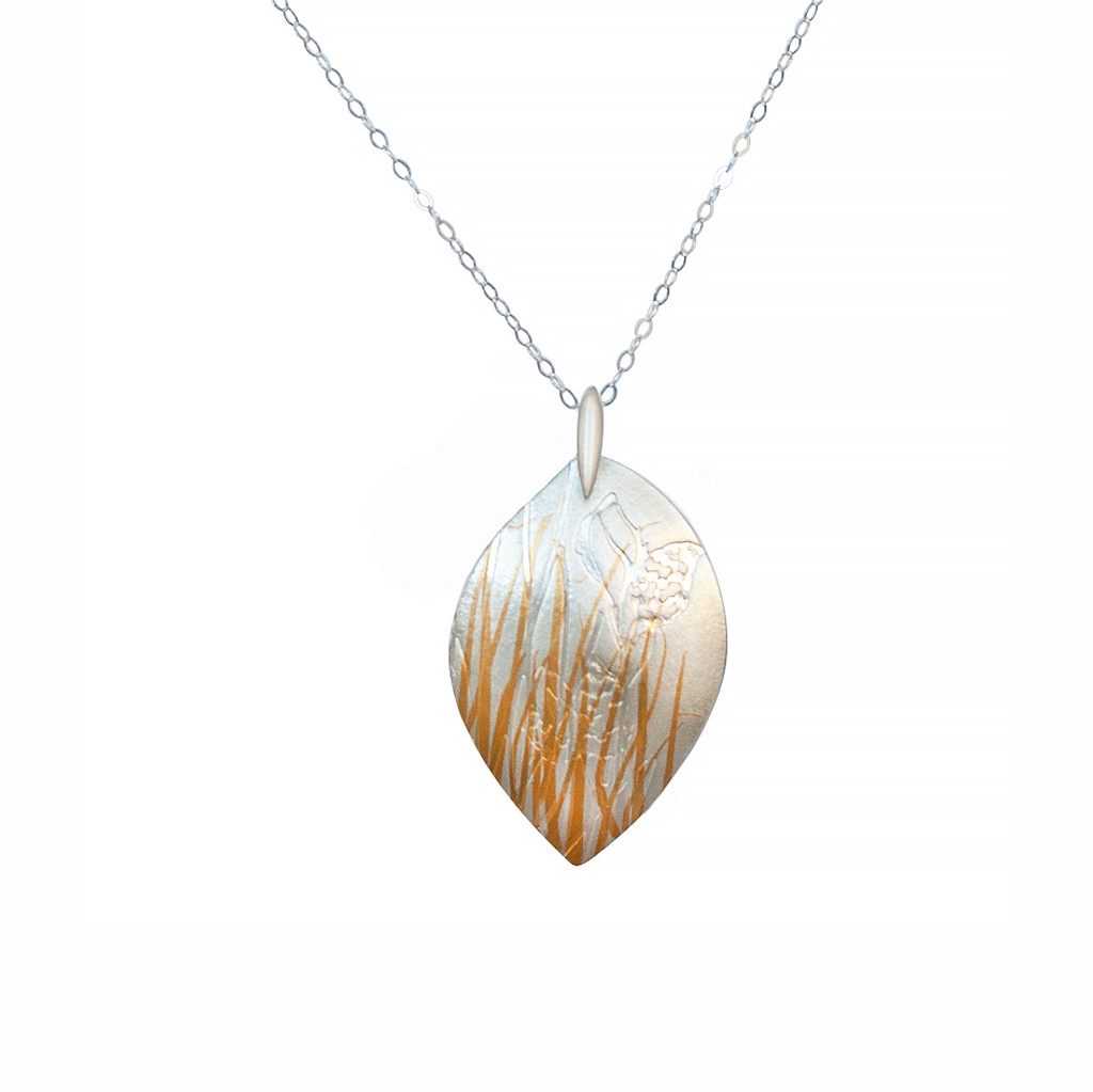 Front view. Luxurious fine silver with fine 24ct gold pendant. Handcrafted using the age old Korean technique of Keum Boo, where 24ct gold is fused to the surface of the silver. The metal is then embossed with specialised templates to create the desired layering of grass and Hakea nut imagery.