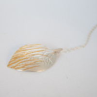 Side view. Luxurious fine silver with fine 24ct gold pendant. Handcrafted using the age old Korean technique of Keum Boo, where 24ct gold is fused to the surface of the silver. The metal is then embossed with specialised templates to create the desired layering of grass and Hakea nut imagery.