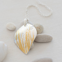Styled image. Luxurious fine silver with fine 24ct gold pendant. Handcrafted using the age old Korean technique of Keum Boo, where 24ct gold is fused to the surface of the silver. The metal is then embossed with specialised templates to create the desired layering of grass and Hakea nut imagery.