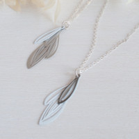 Elegant layered leaf pendant in white based on the varied leaves of native Eremophila plants  Made from stainless steel with contrasting powdercoated colour and raw steel