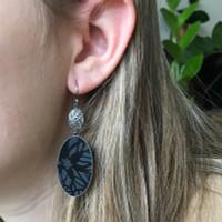 Black daisy silver and aluminium oval earrings