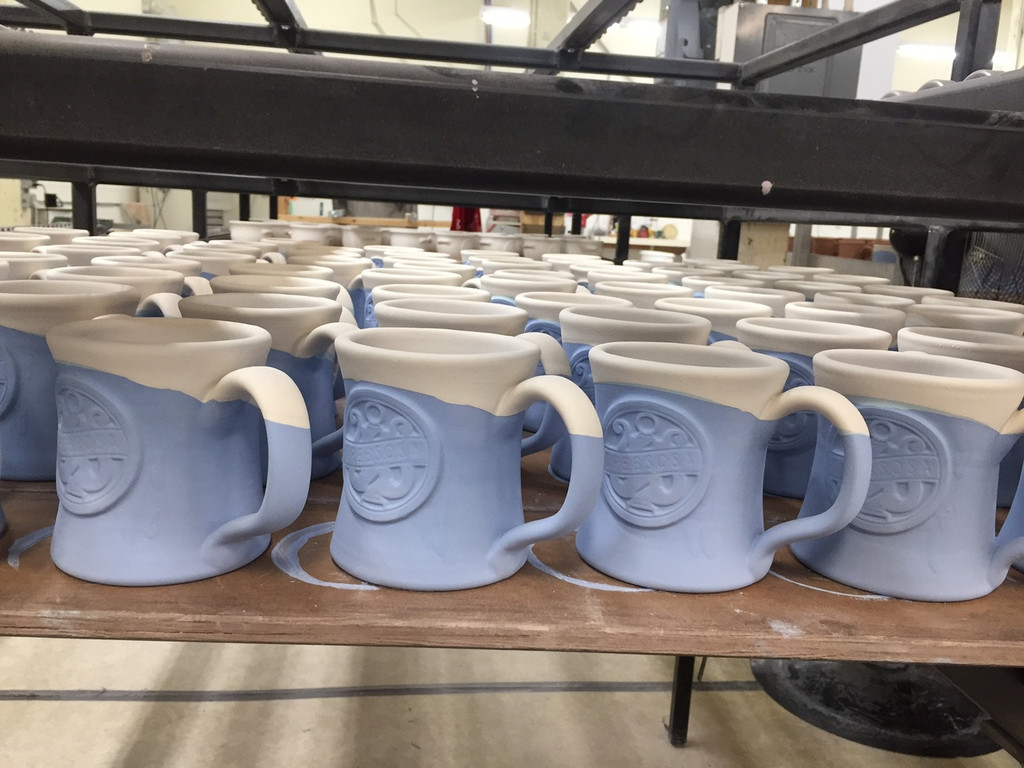 Our new SPEBSQSA 1950's style pottery mug was hand crafted just for you.  Created by Deneen Pottery in St. Paul, Minnesota, each superior quality hand thrown pottery mug features the crisp detailed SPEBSQSA emblem.  Each mug is shaped by over 24 pairs of hands, and although amazingly uniform, no two are exactly the same.   Kiln fired to 2150ºF, this mug is durable and both microwave and dishwasher safe.    All stoneware is lead free & food safe.  The mug is designed with the SPEBSQSA logo and colored in coordination with the design and shape of the mug itself.   Glaze: Navy w/ Powder Blue White, 11 oz.