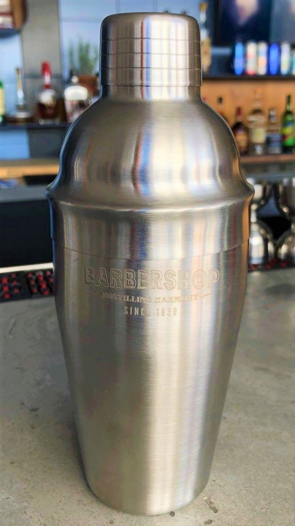 """Brushed stainless steel 18 oz. cocktail shaker. Perfect for crafting your favorite Manhattan or Mojito.  3 part shaker includes built-in strainer/pourer.  Brushed stainless steel 18 oz. cocktail shaker. Perfect for crafting your favorite Manhattan or Mojito.  3 part shaker includes built-in strainer/pourer.  Hand wash only.   Features subtly laser-etched art on front: Barbershop. Distilling harmony since 1938. A part of the """"Barbershop Distilling Harmony"""" Collection."""