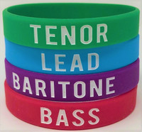 Wear them. Collect them. Share them.  Our silicone wristbands are great for collecting, sharing, gifting, and identifying tag singers.  EVERYONE IN HARMONY on one side and your voice part, whether it be TENOR, LEAD, BARITONE, OR BASS, on the other.  Each wristband is colorfully coordinated with its own voice part:  Green - Tenor, Red - Bass, Blue - Lead, Purple - Baritone.   Part of our Everyone In Harmony Collection.