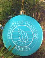 "Celebrate a joyful holiday season with our aqua blue colored shatterproof ornament.  Our dual themed ornament features the BHS logo on one side, and the vintage SPEBSQSA logo on the other.  Don't worry if pesky paws get a hold of the orbs—the shatterproof design prevents messy and dangerous breakage while complementing the nostalgic holiday feel.   A metallic gold top and matching gold string are the perfect finishing touch on this attractive ornament. Size: 3"" x 5/8"".  USA Made."