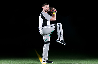 Baseball pitcher wearing leg resistance bands during training to increase his pitching velocity.