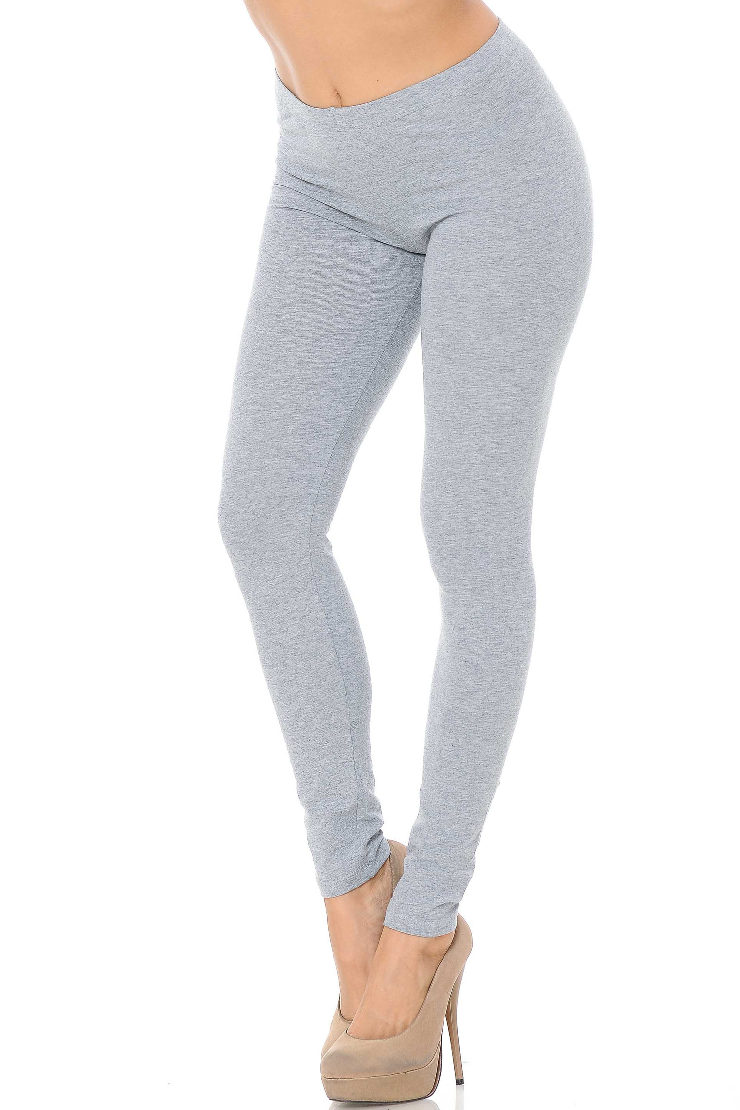 45 degree angle image of female model wearing a heather gray pair of made in the USA cotton leggings showing  a just below the belly button rise and full length going to the ankles.
