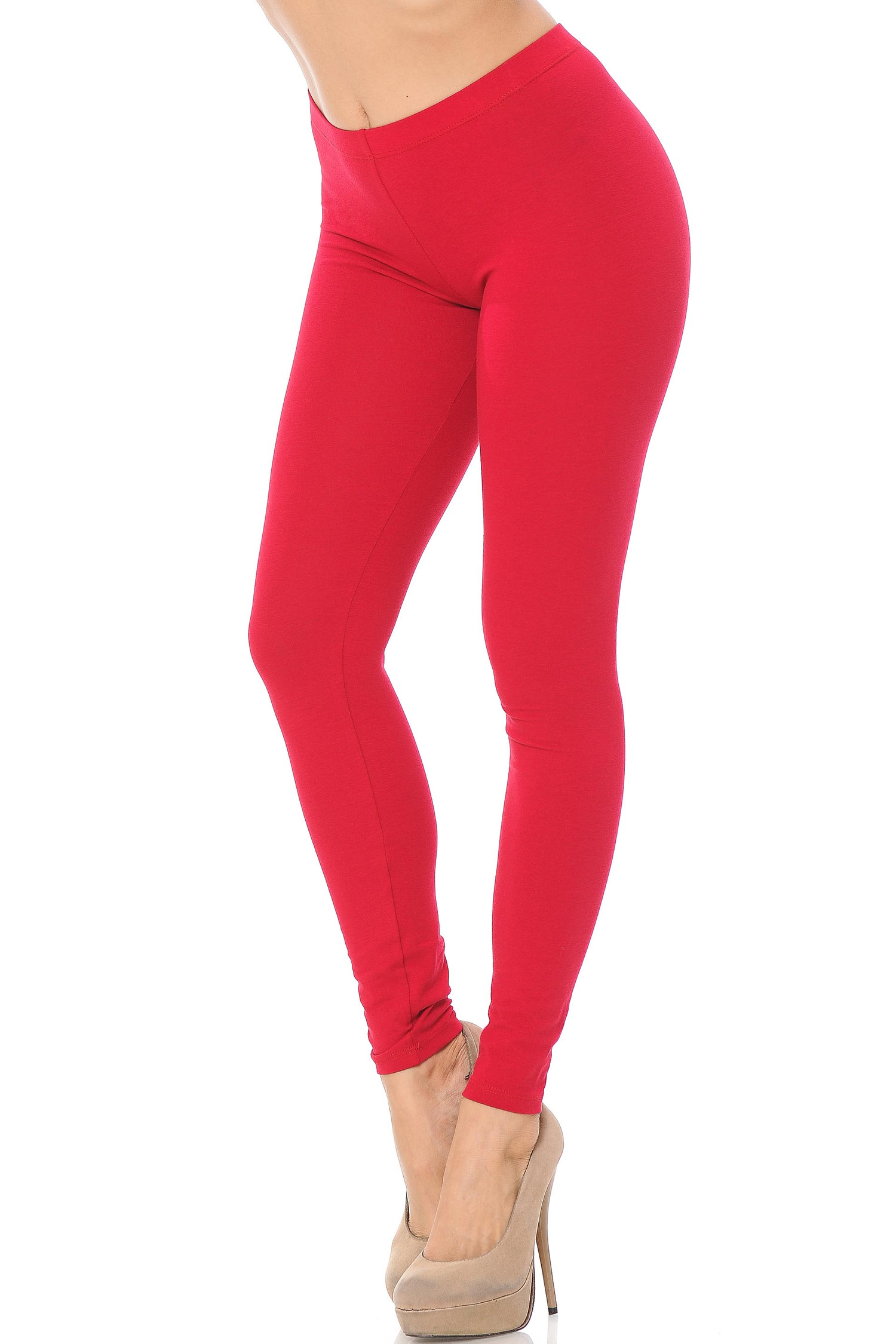 45 degree angle image of female model wearing a red pair of made in the USA cotton leggings showing  a just below the belly button rise and full length going to the ankles.
