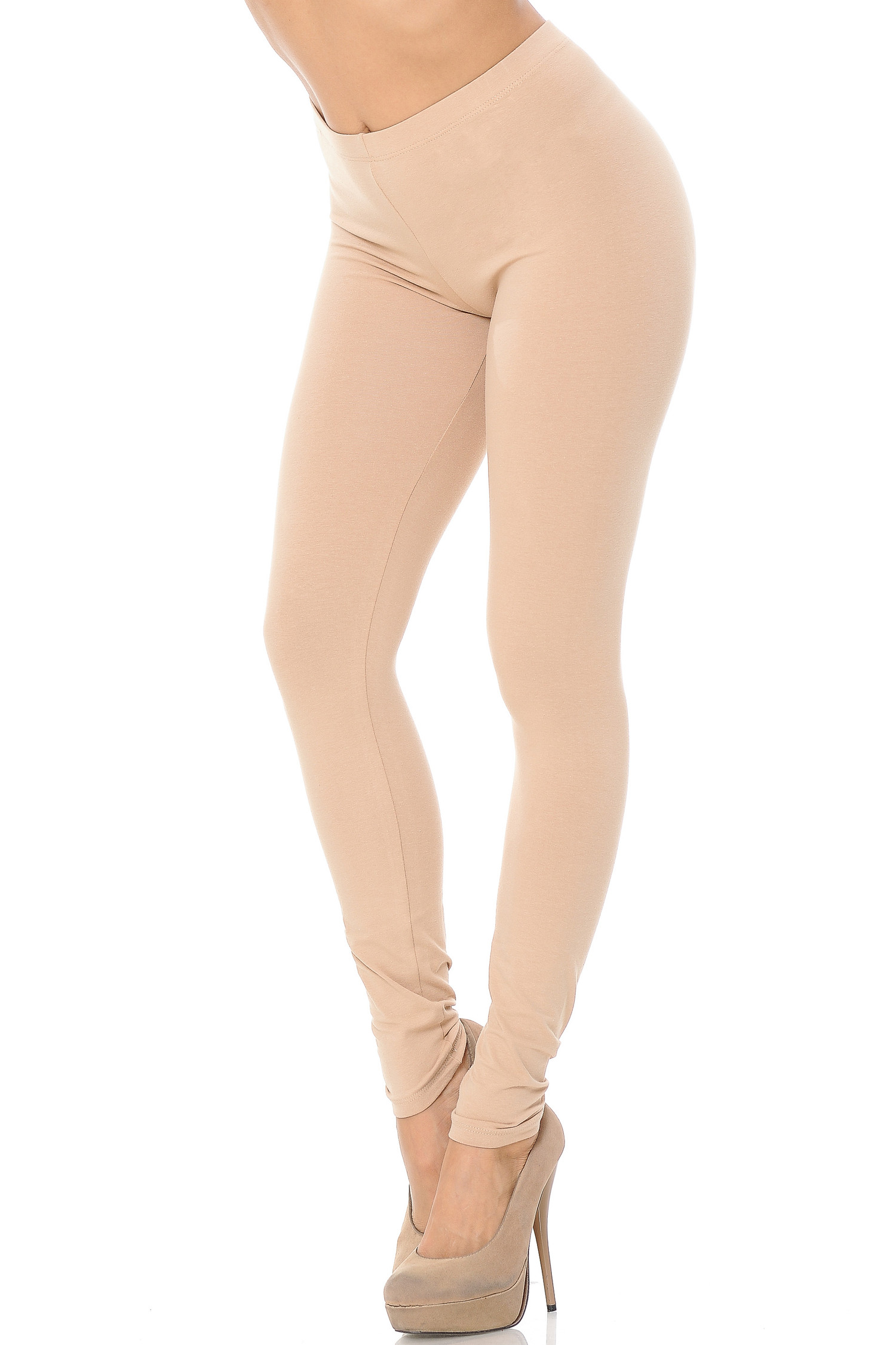 45 degree angle image of female model wearing a beige pair of made in the USA cotton leggings showing  a just below the belly button rise and full length going to the ankles.