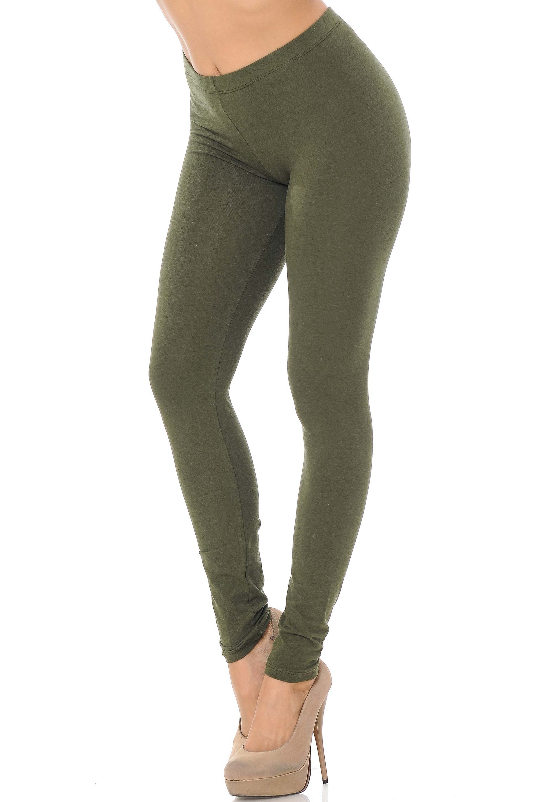45 degree angle image of female model wearing an olive pair of made in the USA cotton leggings showing  a just below the belly button rise and full length going to the ankles.