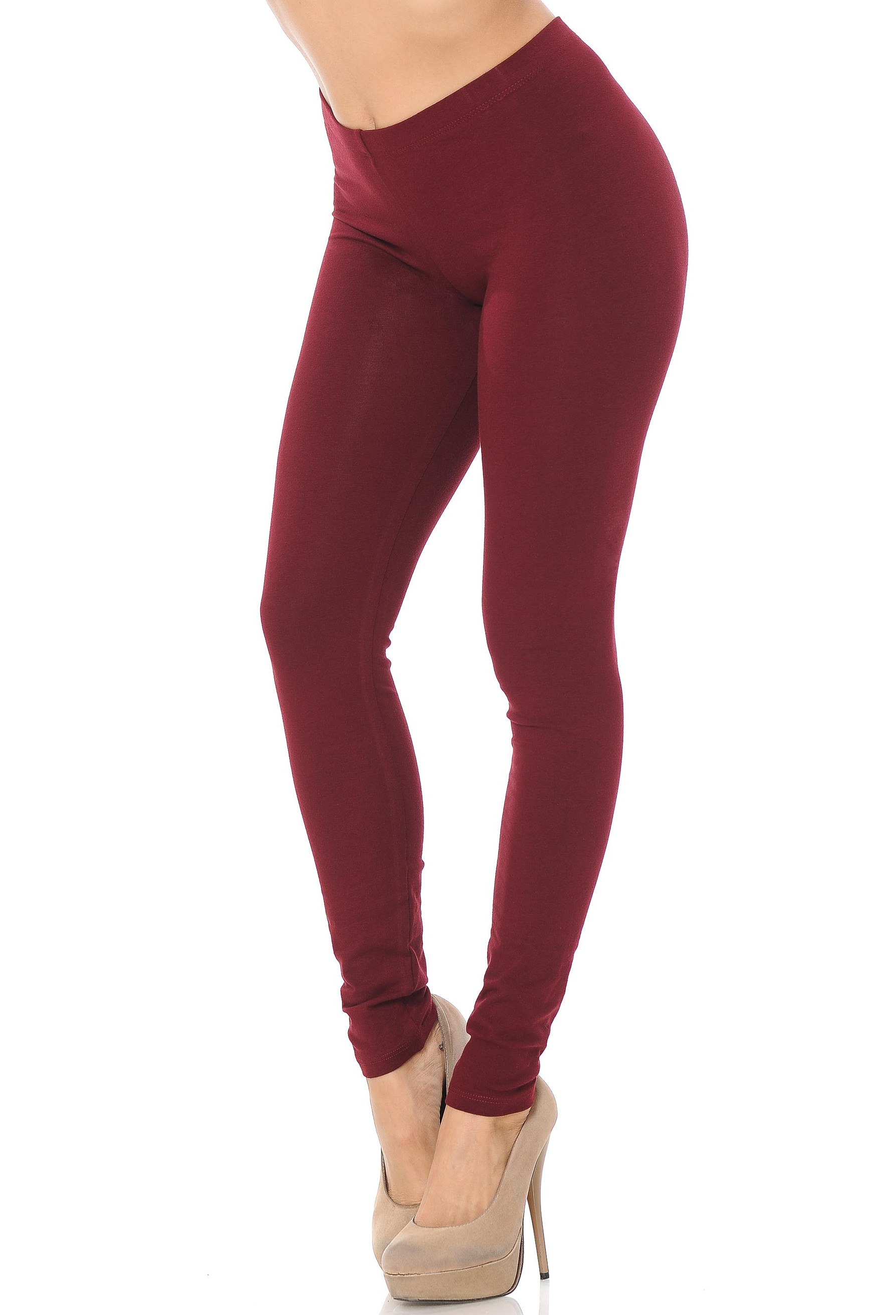 45 degree angle image of female model wearing a burgundy pair of made in the USA cotton leggings showing  a just below the belly button rise and full length going to the ankles.