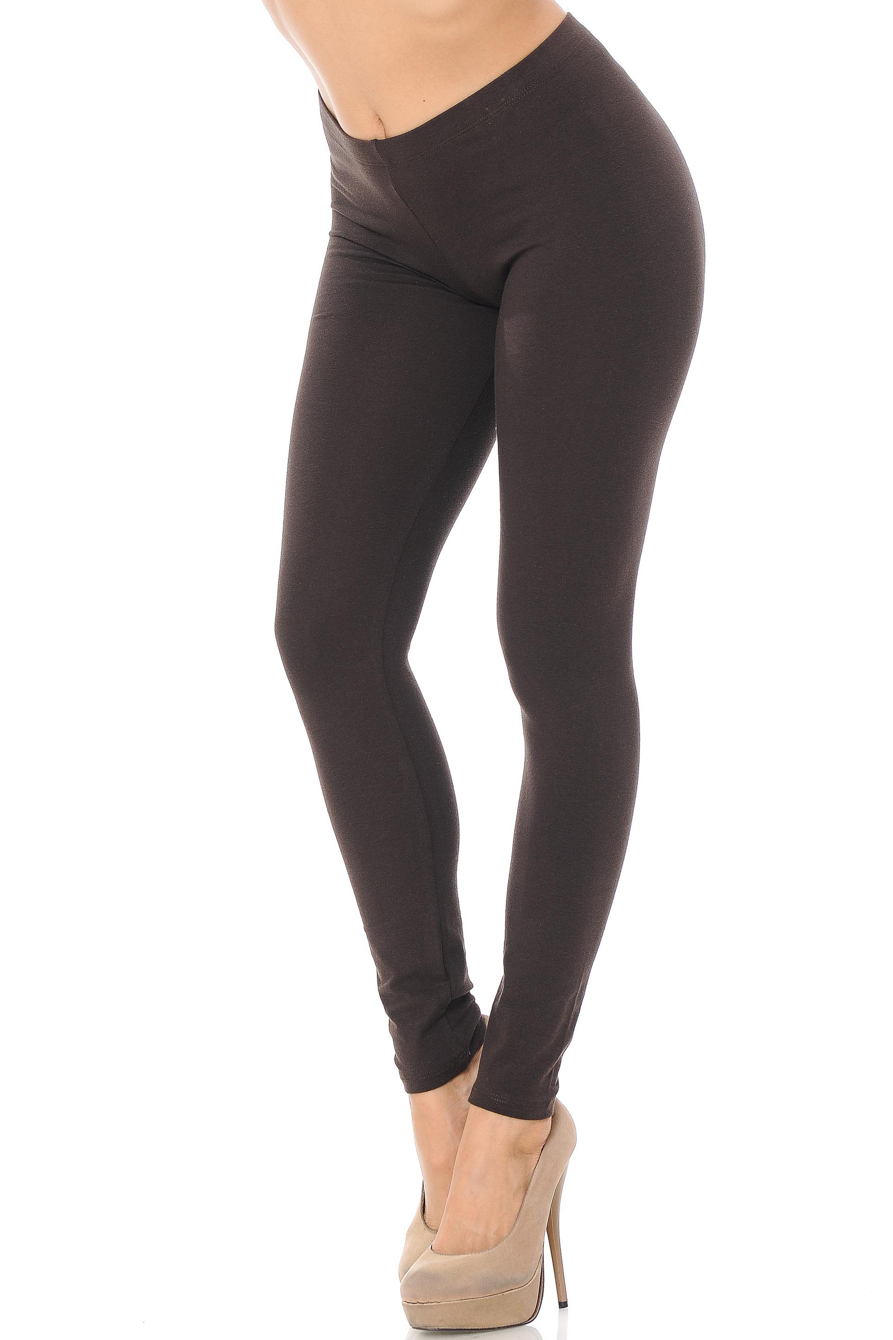 45 degree angle image of female model wearing a brown pair of made in the USA cotton leggings showing  a just below the belly button rise and full length going to the ankles.