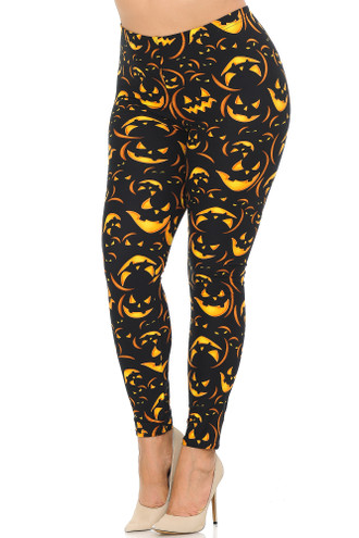 Left side view of our Buttery Soft Evil Halloween Pumpkins Plus Size Leggings featuring lit up orange glowing jack-o-lantern faces contrasting a black background.