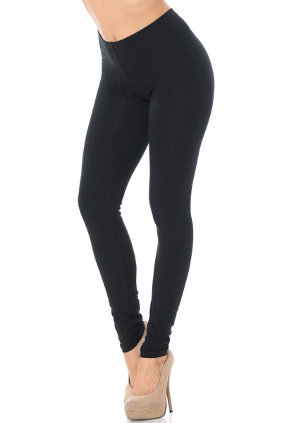 45 degree angle image of female model wearing a black pair of made in the USA cotton leggings showing  a just below the belly button rise and full length going to the ankles.