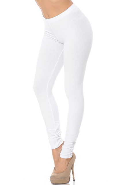 45 degree angle image of female model wearing a white pair of made in the USA cotton leggings showing  a just below the belly button rise and full length going to the ankles.