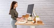 """60"""" x 30"""" maple GREENGUARD-certified laminate desk on a white UPLIFT V2 Standing Desk Frame"""