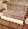 """Zip-Up Carpet protection film from www.leadPaintEPAsupplies.com, The Renovators Supply Store.  36"""" x 200' Peel and stick adhesive technology being placed on steps."""