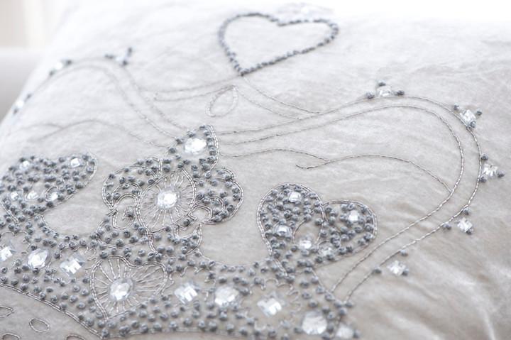 Silver hand embroidery and diamanté crystal crown on luxury cream velvet cushion.