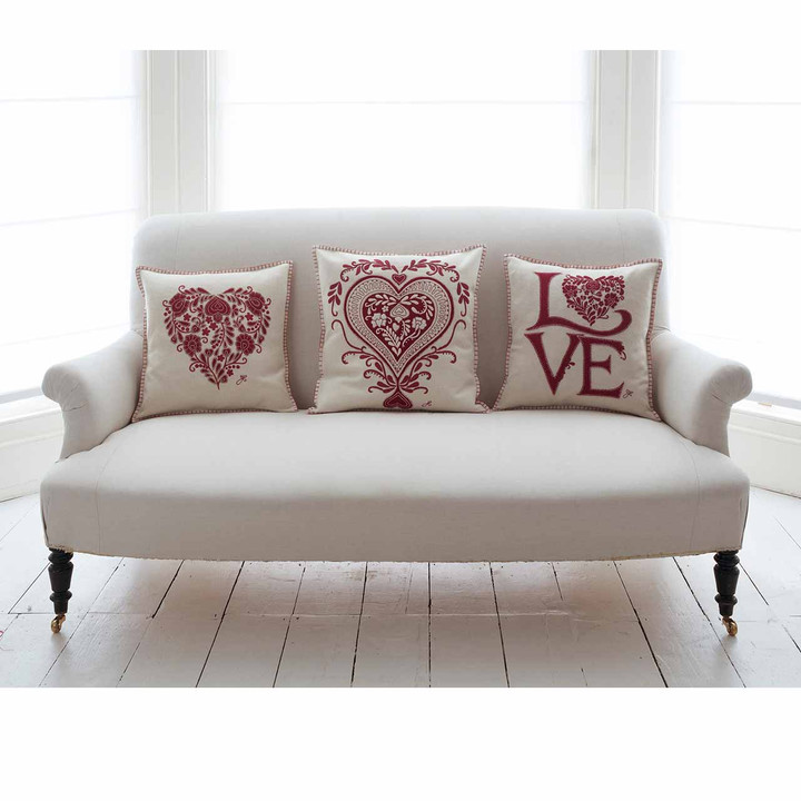 Cream luxury Romany Heart cushion with hand embroidered appliqué red flowers and and leaf motifs.