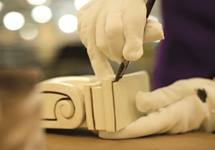 Gloved hands of a KraftMaid finish artisan applying glaze highlights to a corbel