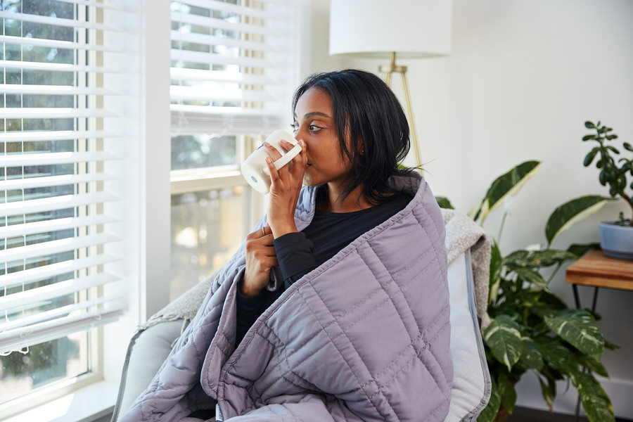 Woman drinking coffee while wearing Moonbow Cooling Weighted Blanket