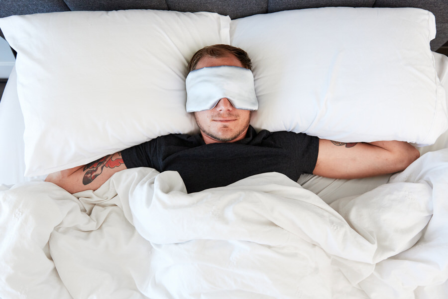 Man sleeping with Moonbow Total Dark Satin Eye Mask