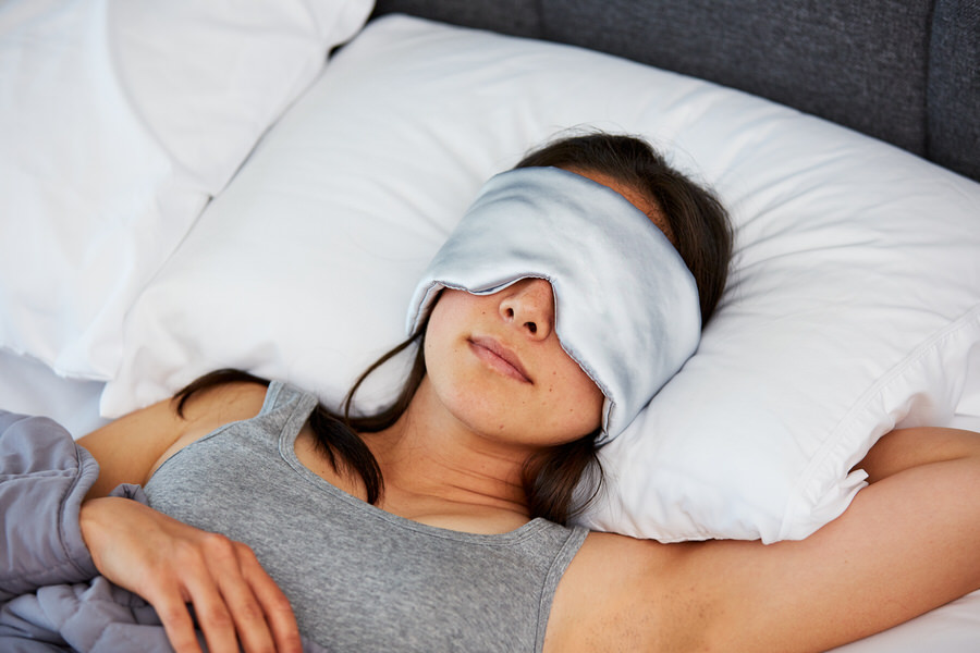 Woman sleeping with Moonbow Total Dark Satin Eye Mask